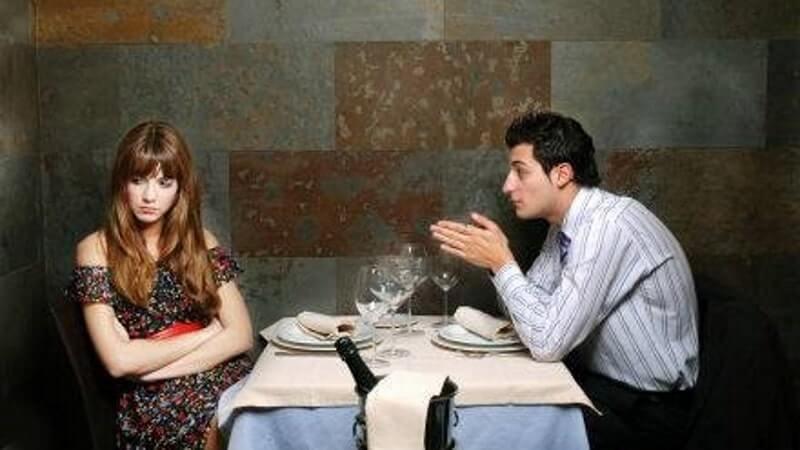 Mann und Frau sitzen am Tisch und haben Streit