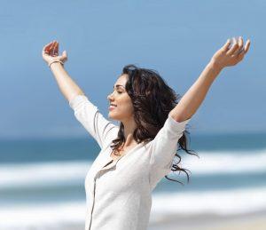 Frau am Meer strahlt und ist glücklich