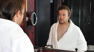 Mann im Bademantel schaut sich im Spiegel