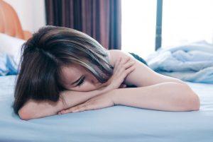 Frau ist traurig und liegt auf Bett
