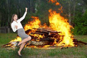 Frau freut sich, hinter ihr ist ein großes Feuer
