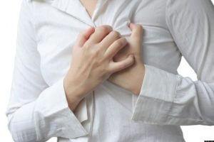 Frau hat Herzschmerz und fast sich an Brust