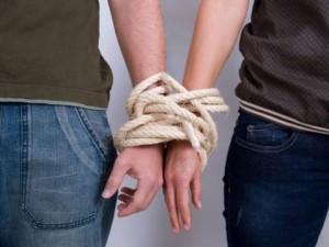 Mann und Frau sind am Handgelenk zusammen geschnürrt