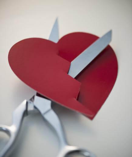 Herz wird mit Schere durchschnitten