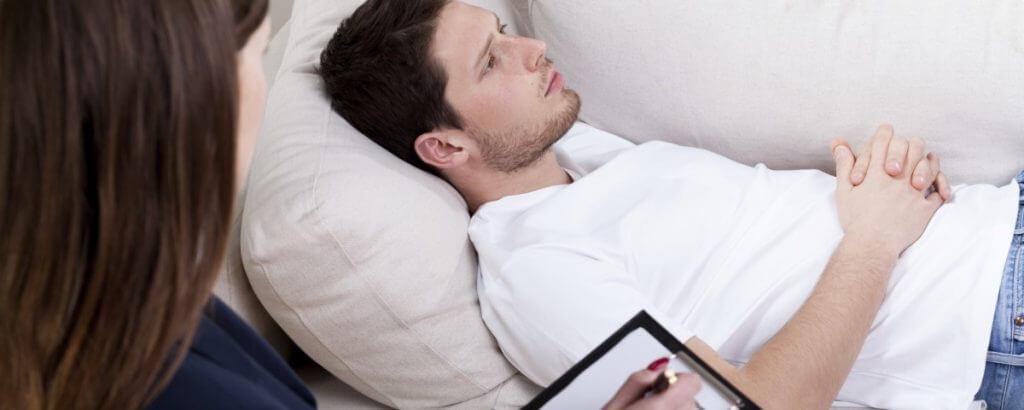 Mann liegt auf Sofa und denkt nach