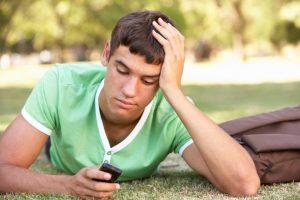 Junger Mann mit Handy liegt auf der Wiese