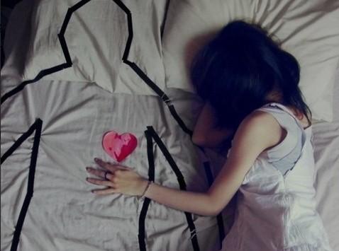 Frau liegt auf Bett und vermisst ihren Ex