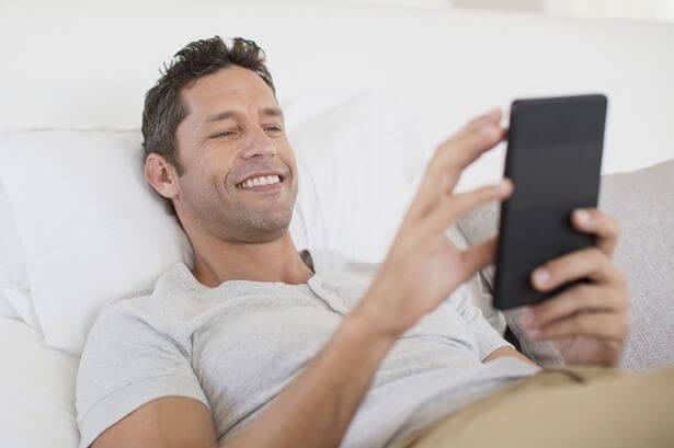 Mann liegt im Bett und schreibt seiner Ex auf dem Handy