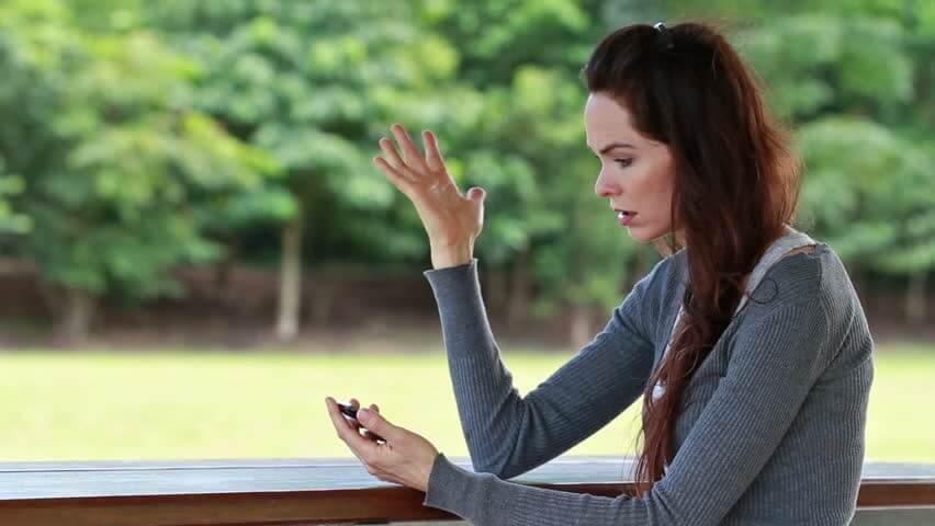 Frau sieht etwas auf dem Handy und ist wütend